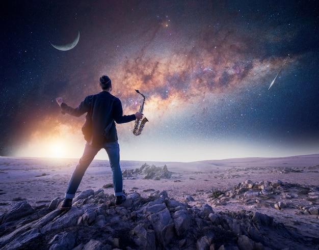 Silhueta de um músico ou saxofonista de braços abertos em uma rocha sob a via láctea
