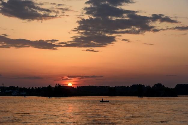 Silhueta de um navio de pesca na margem do rio angara, sob o sol e as nuvens do pôr do sol