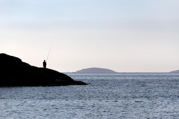 Silhueta de um pescador de pé nas rochas com vara de pescar perto do mar em dia ensolarado.