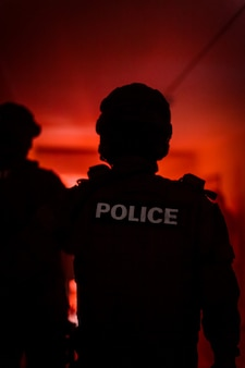 Silhueta de um policial. comando da polícia em ação, prendendo o agressor no prédio