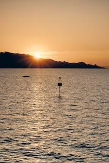 Silhueta de um sinal na água com o sol brilhando atrás da montanha