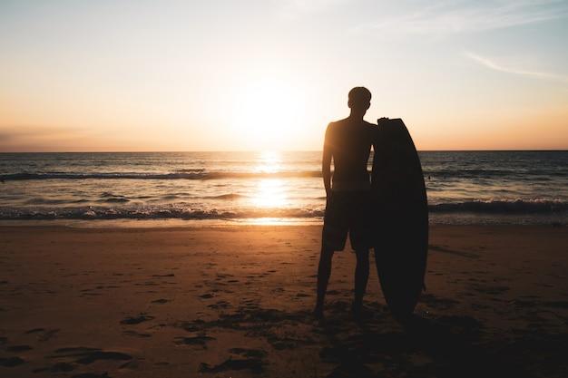 Silhueta de um surfista carregando suas pranchas de surf na praia do pôr do sol com a luz do sol