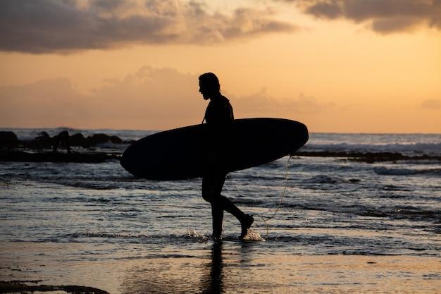 Silhueta de um surfista saindo da água durante o pôr do sol com sua prancha