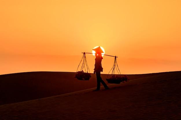 Silhueta de um vendedor ambulante viajando pelo deserto de mui ne no vietnã