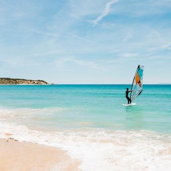 Silhueta de um windsurfer no mar azul.