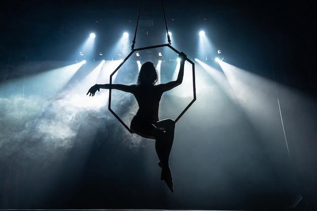 Silhueta de uma acrobata aérea feminina no palco do circo com luzes pontuais na superfície