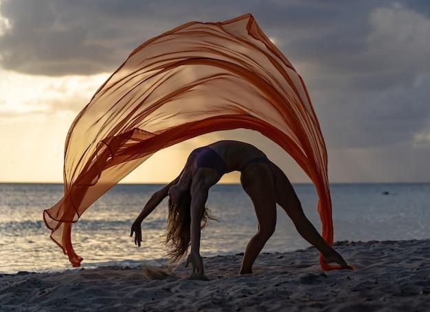 Silhueta de uma acrobata feminina flexível fazendo truques com seda durante o dramático pôr do sol com nuvens tempestuosas na paisagem marítima