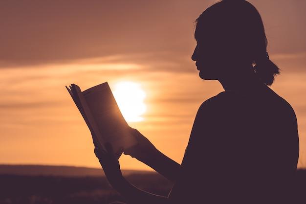 Silhueta de uma bela jovem ao amanhecer sentada no chão e olhando cuidadosamente para o livro aberto
