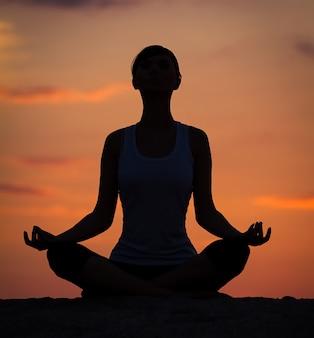 Silhueta de uma bela mulher de ioga pela manhã