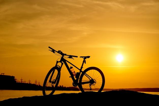 Silhueta de uma bicicleta ao pôr do sol