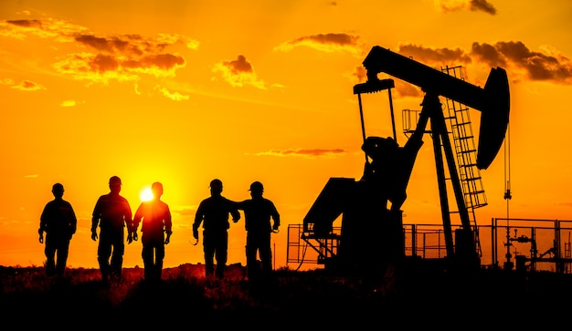 Silhueta de uma bomba de óleo bruto de trabalhador de campo petrolífero ao pôr do sol.