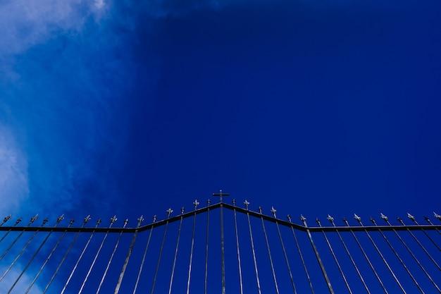 Silhueta de uma cerca de cemitério assustador com céu azul ao fundo.