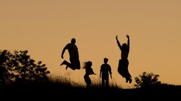 Silhueta de uma família feliz de quatro, mãe, pai, filha, filho ao pôr do sol