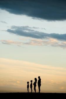 Silhueta de uma família, ordenada do mais alto para o mais baixo, na praia
