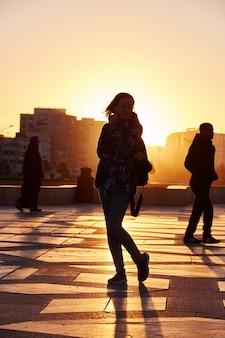 Silhueta de uma garota ao pôr do sol no inverno em casablanca, marrocos. sol se põe atrás da garota