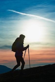 Silhueta de uma garota em uma montanha durante uma caminhada religiosa