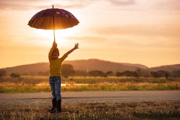 Silhueta de uma garota feliz com guarda-chuva ao pôr do sol