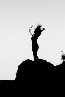 Silhueta de uma garota no topo de uma montanha.
