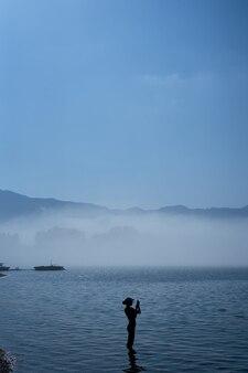 Silhueta de uma garota parada no mar tirando fotos no telefone