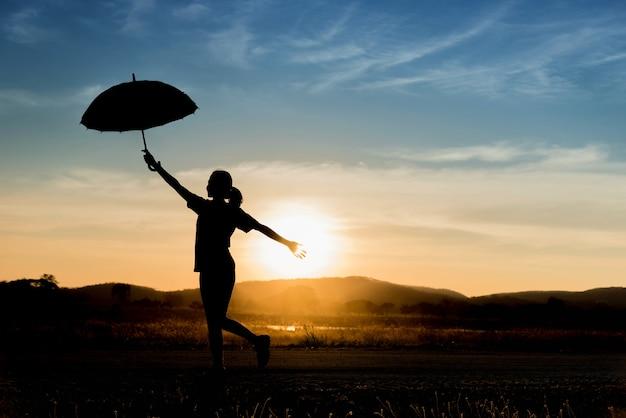 Silhueta de uma jovem feliz com guarda-chuva ao pôr do sol.