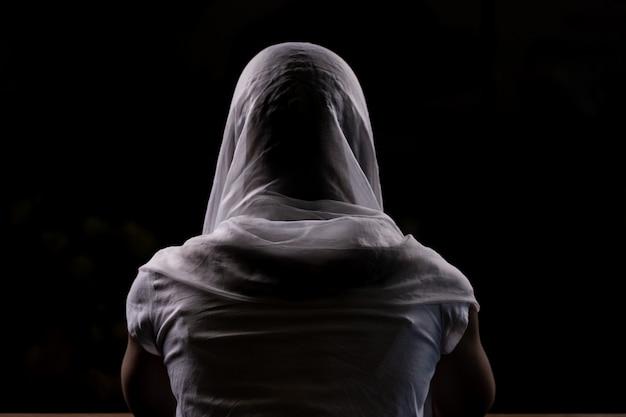 Silhueta de uma jovem garota que se senta na igreja e orando