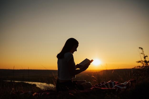Silhueta de uma jovem mulher bonita ao pôr do sol sentado em uma manta e olhando cuidadosamente para o livro aberto.