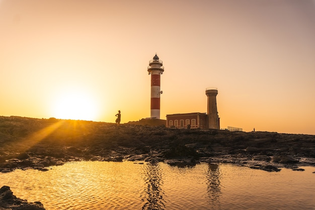 Silhueta de uma jovem no pôr do sol no farol de toston, punta ballena, perto da cidade de el cotillo, ilha de fuerteventura, nas ilhas canárias. espanha