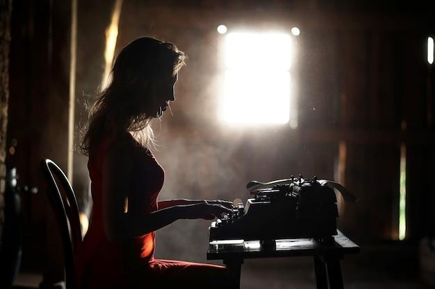 Silhueta de uma linda garota em um vestido vermelho no fundo de uma janela em uma casa velha