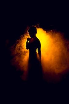Silhueta de uma linda garota na fumaça, magia de fogo
