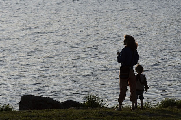 Silhueta de uma mãe e seu filho contra uma lagoa ao pôr do sol