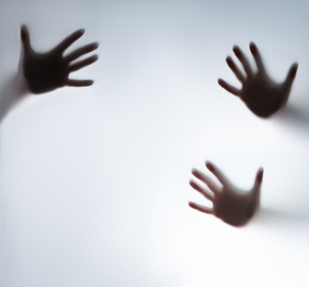 Silhueta de uma mão atrás do vidro