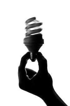 Silhueta de uma mão segurando uma lâmpada em espiral
