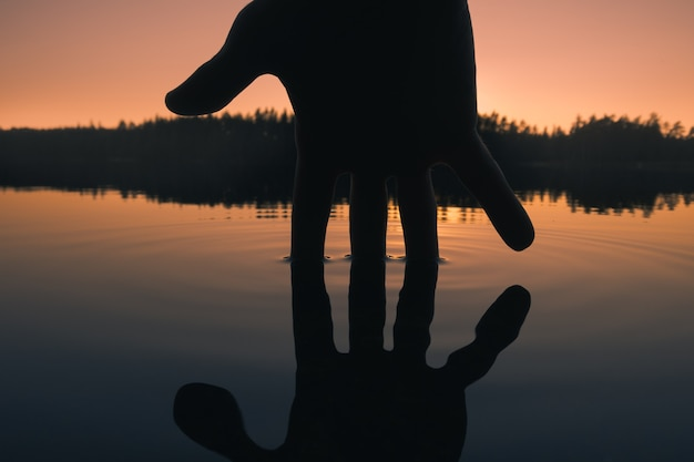Silhueta de uma mão tocando a superfície da água. impacto humano no meio ambiente
