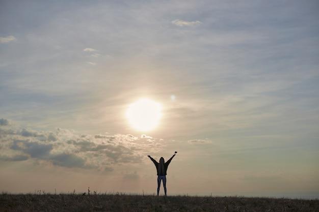 Silhueta de uma menina com cabelo comprido que fica em uma colina com as mãos levantadas ao amanhecer o sol sh ...
