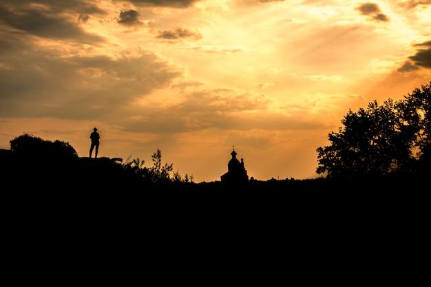 Silhueta de uma menina e a igreja ortodoxa contra o céu. suzdal, rússia