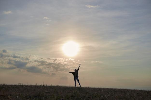 Silhueta de uma menina em roupas esportivas que fica na colina levantando as mãos contra o background ...