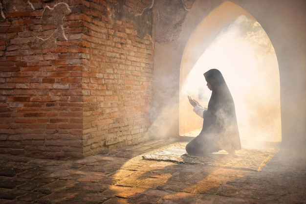 Silhueta de uma menina muçulmana orando e fazendo um pedido a alá na velha mesquita, província de phra nakhon si ayutthaya, tailândia