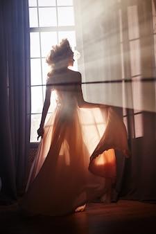 Silhueta de uma menina mulher sexy perto da janela no sol da manhã à noite. moda mulher loira nos raios de sol. a luz solar cai no corpo de uma mulher. luz mágica de fada na janela