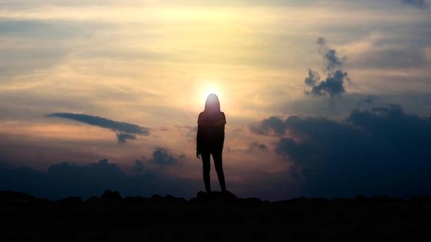 Silhueta de uma menina olhando o pôr do sol