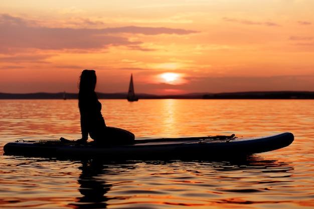 Silhueta de uma menina sentada em uma prancha de remo ao pôr do sol
