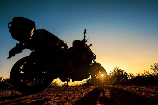 Silhueta de uma moto de turismo estacionada ao pôr do sol
