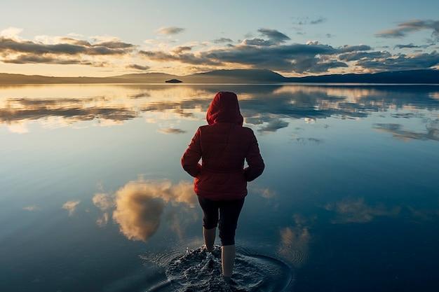 Silhueta de uma mulher deitada de costas dentro de um lago tranquilo onde as nuvens e o céu azul se refletem