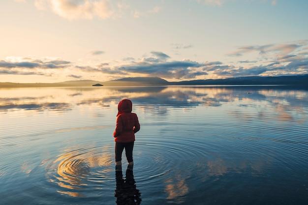 Silhueta de uma mulher deitada de costas dentro de um lago tranquilo onde as nuvens e o céu azul