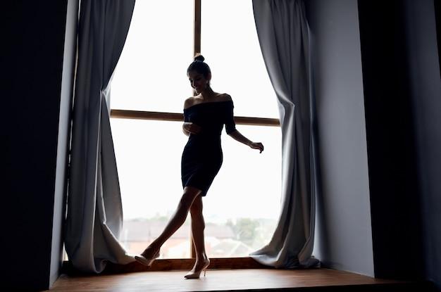Silhueta de uma mulher em crescimento total em um modelo de janela e cortinas cinza