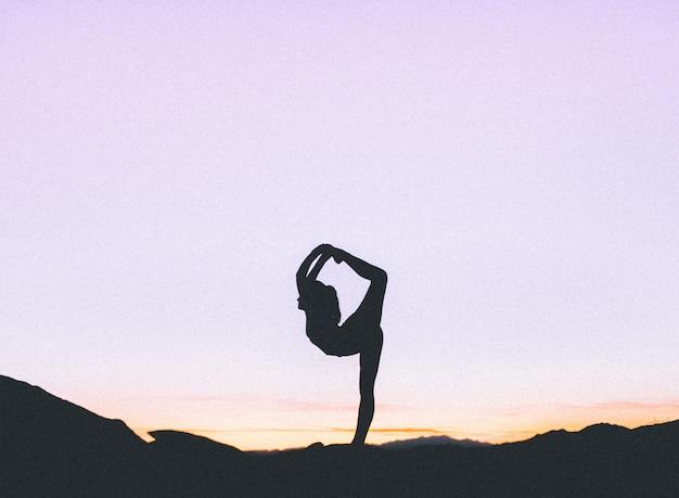 Silhueta de uma mulher em forma praticando ioga em um penhasco alto ao pôr do sol