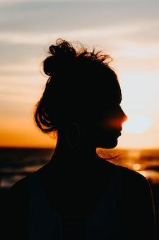 Silhueta de uma mulher em pé na costa do mar com um belo pôr do sol