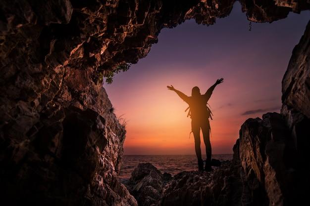Silhueta de uma mulher em pé na entrada da caverna