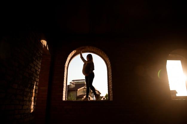 Silhueta de uma mulher grávida em um pôr do sol