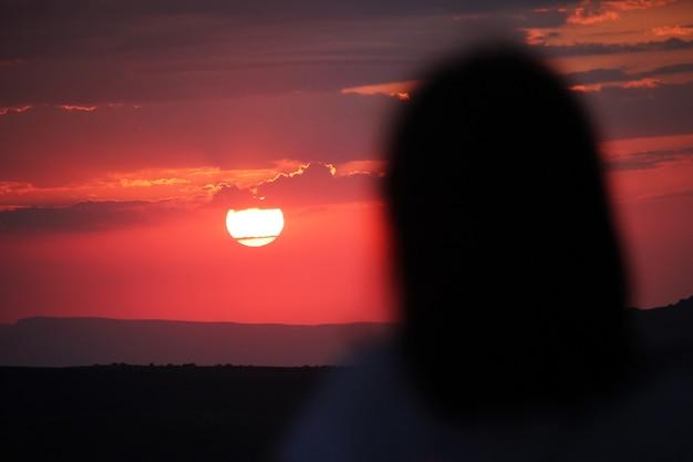 Silhueta de uma mulher olhando para um pôr do sol vermelho jovem mulher na luz do sol, olhando para longe