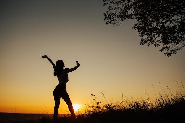 Silhueta de uma mulher segurando um telefone e tomando selfie do lado de fora durante o pôr do sol.
